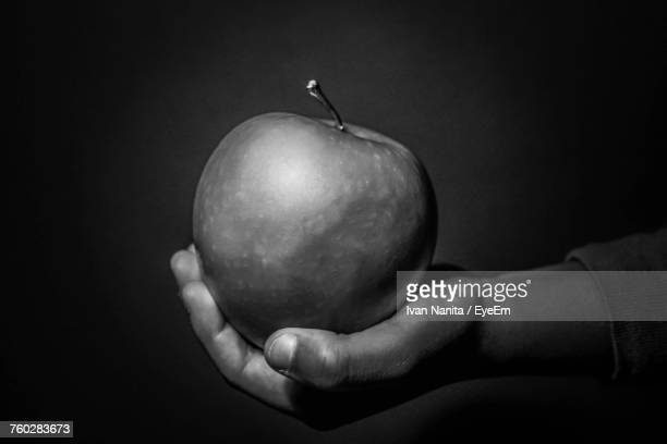 Cropped Hand Holding Apple Against Black Background