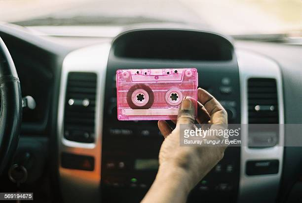 Cropped hand holding audio cassette in car