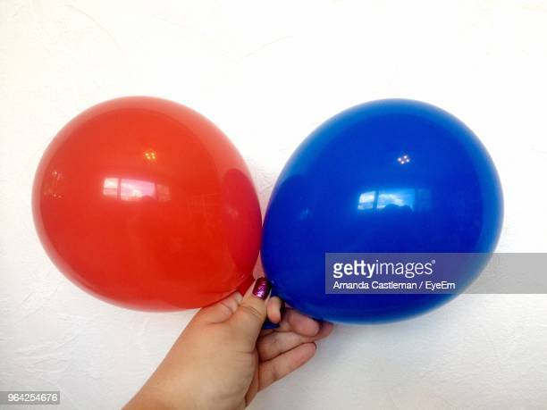 Cropped Hand Holding Balloons Against Wall