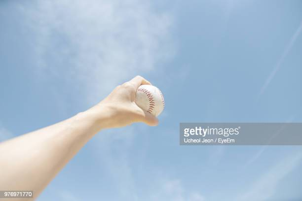 cropped hand holding baseball against sky - korean baseball stock pictures, royalty-free photos & images