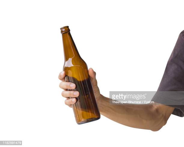 cropped hand holding beer bottle against white background - mano humana fotografías e imágenes de stock
