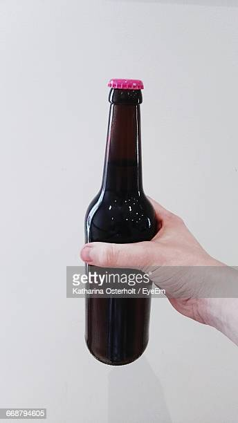 Cropped Hand Holding Beer Bottle Against White Background