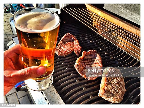 Cropped Hand Holding Beer Glass Over Steak On Barbecue Grill