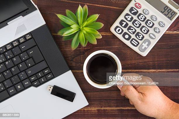Cropped Hand Holding Black Coffee By Laptop On Table
