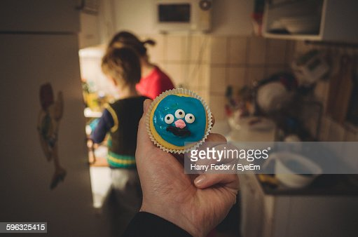 Cropped Hand Holding Blue Cupcake At Kitchen