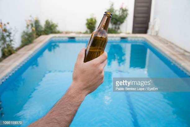 cropped hand holding bottle against swimming pool - liquor bottles stock pictures, royalty-free photos & images