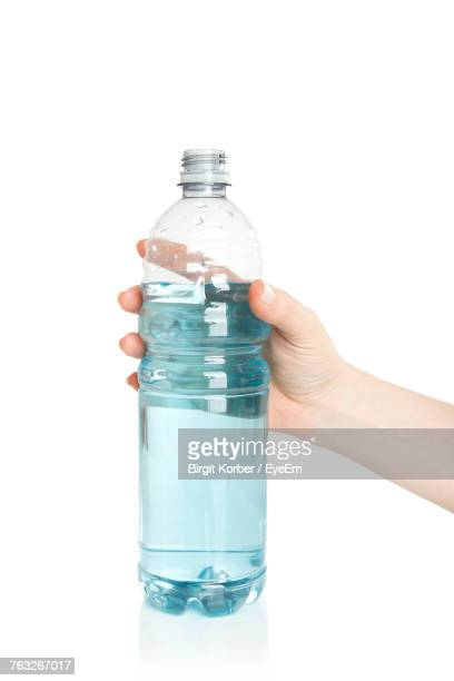 Cropped Hand Holding Bottle Against White Background