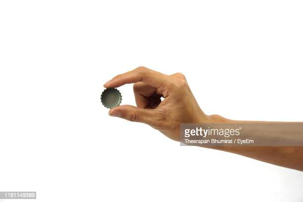 cropped hand holding bottle cap against white background - lid stock photos and pictures