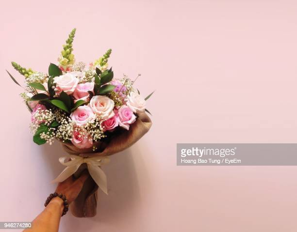 cropped hand holding bouquet against pink background - bunch stock pictures, royalty-free photos & images