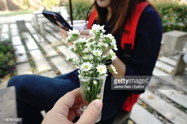 Cropped Hand Holding Bouquet Towards Woman Using Phone