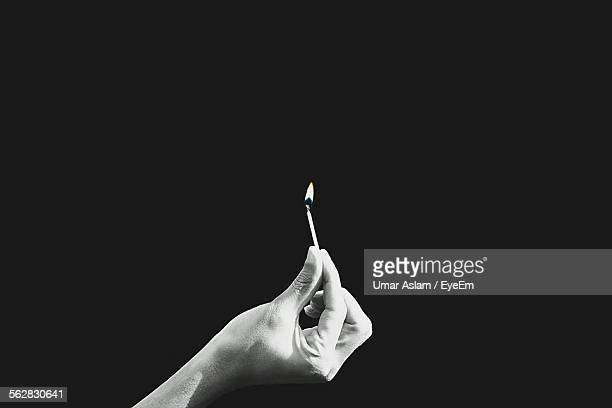Cropped Hand Holding Burning Matchstick Against Black Background