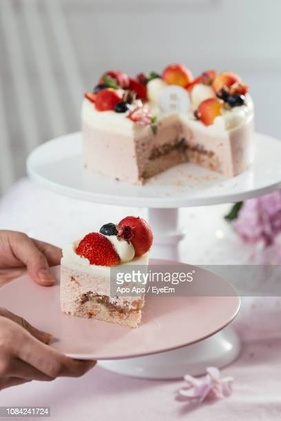 Cropped Hand Holding Cake Slice In Plate During Celebration