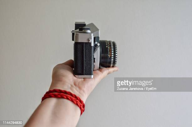 cropped hand holding camera against wall - zuzana janekova stock pictures, royalty-free photos & images