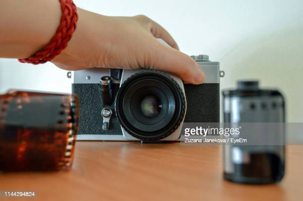 cropped hand holding camera at table - zuzana janekova stock pictures, royalty-free photos & images