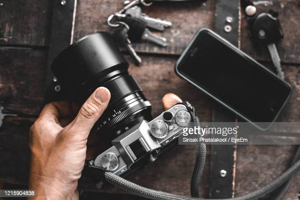 cropped hand holding camera by smart phone on table - camera photographic equipment stock pictures, royalty-free photos & images