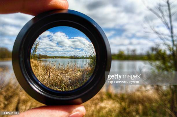 cropped hand holding camera lens against lake - lens optical instrument stock photos and pictures