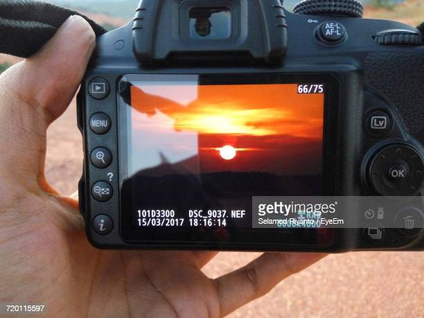 Cropped Hand Holding Camera With Sunset Photograph