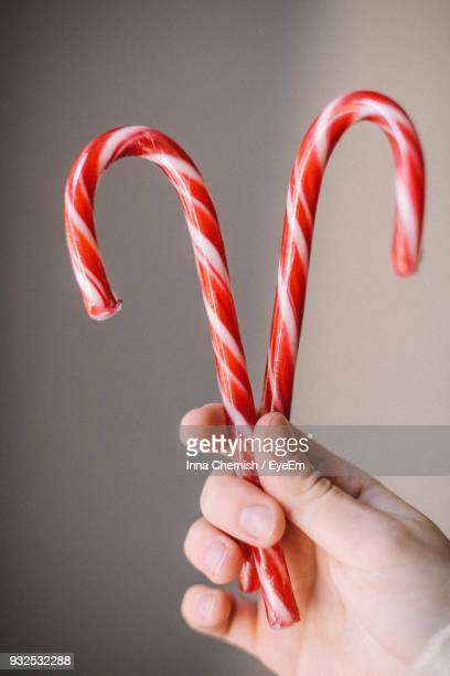 Cropped Hand Holding Candy Canes Against Wall