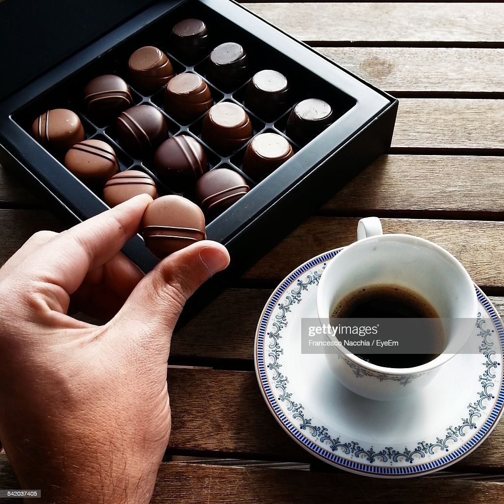 Cropped Hand Holding Chocolate Piece While Having Coffee At Home : Stock Photo