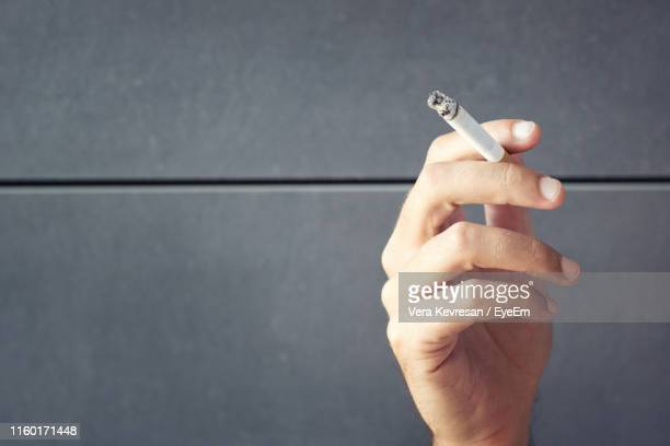 cropped hand holding cigarette against gray wall - ash stock photos and pictures