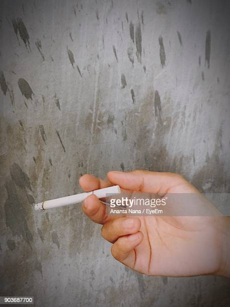 Cropped Hand Holding Cigarette Against Wall