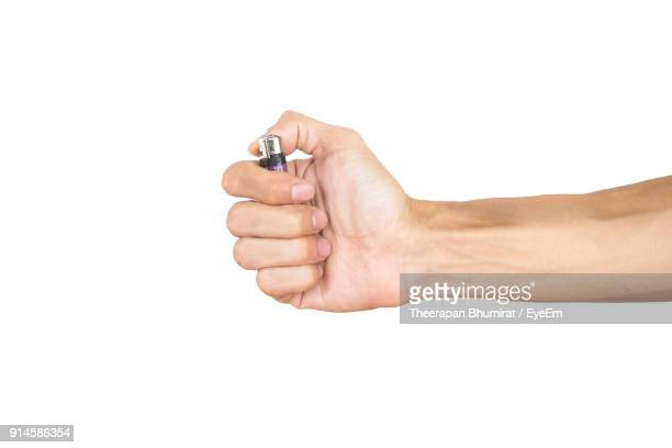 cropped hand holding cigarette lighter against white background - cigarette lighter stock pictures, royalty-free photos & images