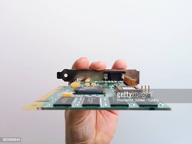 Cropped Hand Holding Circuit Board Against White Background