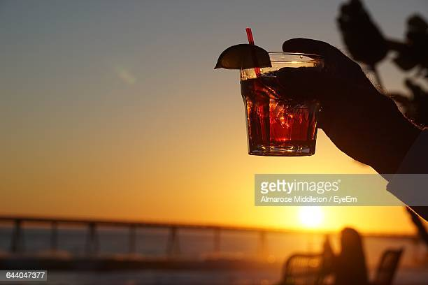 Cropped Hand Holding Cocktail Against Sky During Sunset