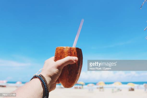 Cropped Hand Holding Coconut Against Blue Sky At Beach During Sunny Day