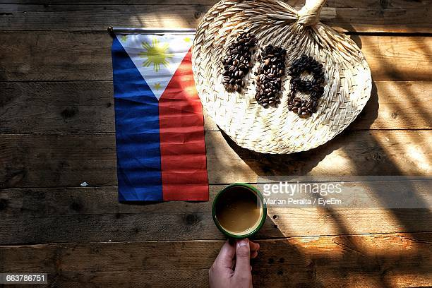 cropped hand holding coffee in front of philippines flag and number on table - philippines flag stock pictures, royalty-free photos & images