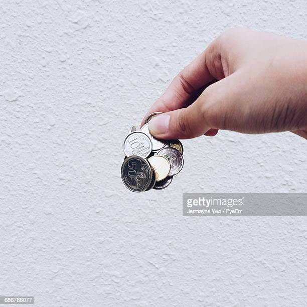 Cropped Hand Holding Coins By White Wall