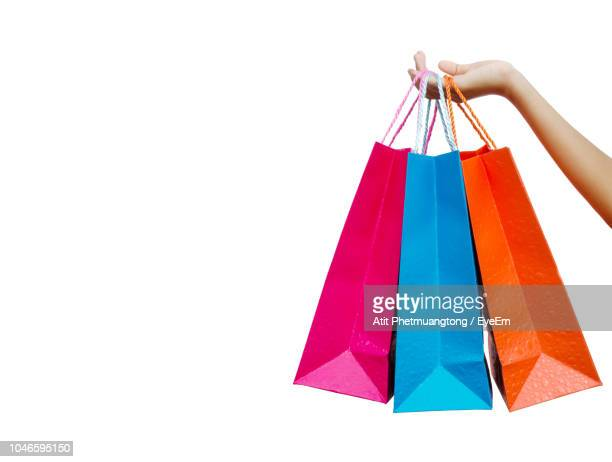 cropped hand holding colorful shopping bags against white background - 買い物袋 ストックフォトと画像