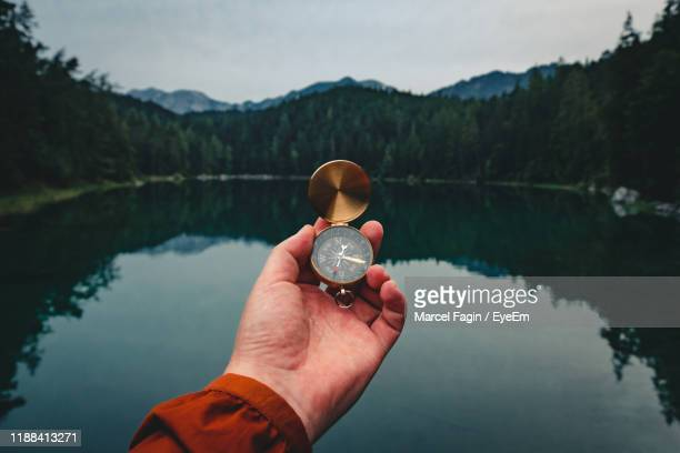 cropped hand holding compass against lake in forest - compass stock pictures, royalty-free photos & images