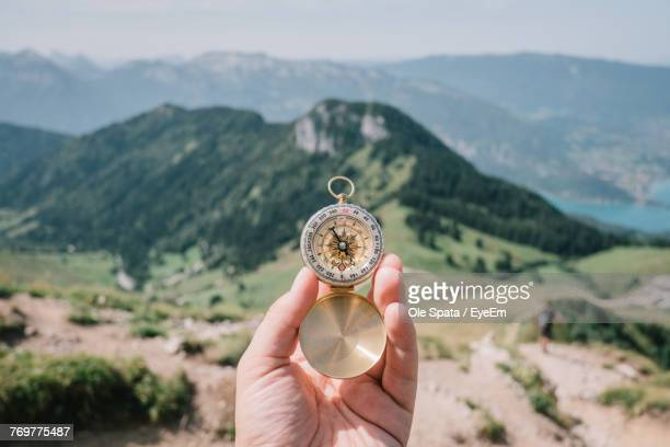 cropped hand holding compass against mountains - compass stock pictures, royalty-free photos & images