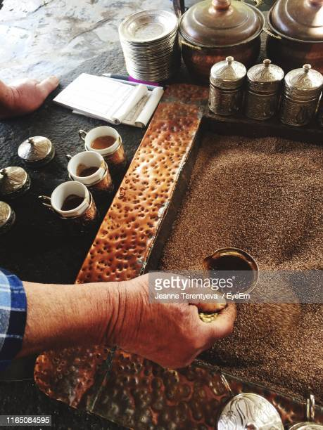 Cropped Hand Holding Container In Coffee Beans