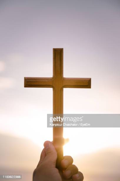 cropped hand holding cross against sky during sunset - easter cross stock pictures, royalty-free photos & images