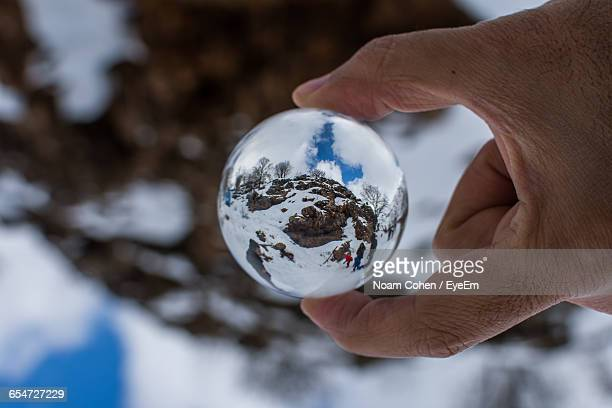 Cropped Hand Holding Crystal Ball On Landscape During Winter With Reflection