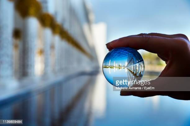 cropped hand holding crystal ball over lake - transparent stock pictures, royalty-free photos & images