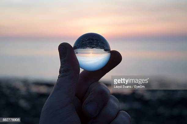 Cropped Hand Holding Crystal Ball With Reflection At Sunset