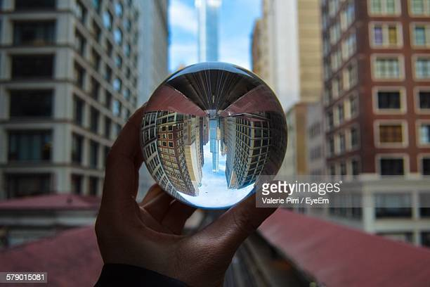 Cropped Hand Holding Crystal Ball With Reflection In City