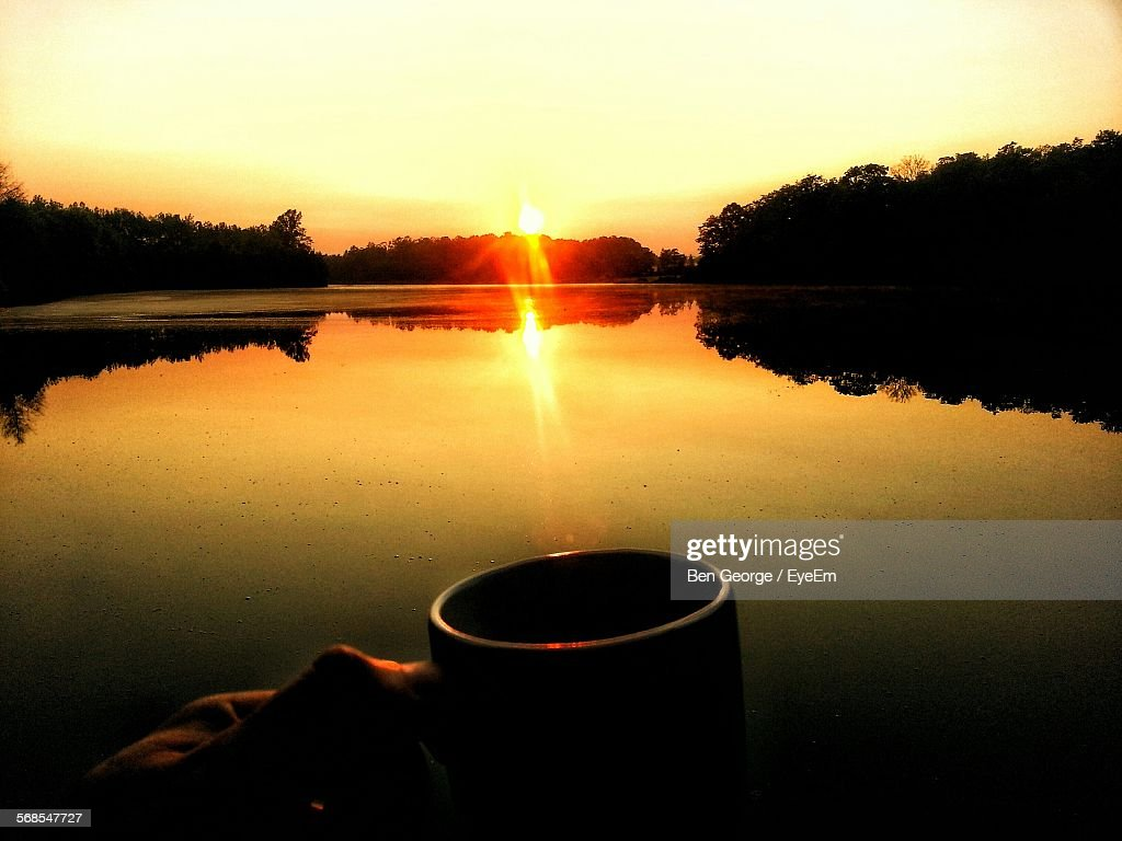 Cropped Hand Holding Cup Against Lake : Stock Photo