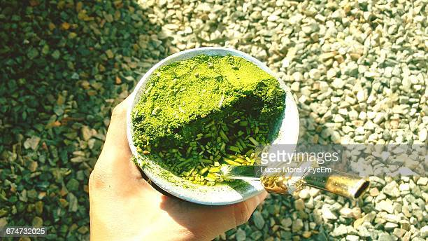 Cropped Hand Holding Cup With Yerba Mate On Field