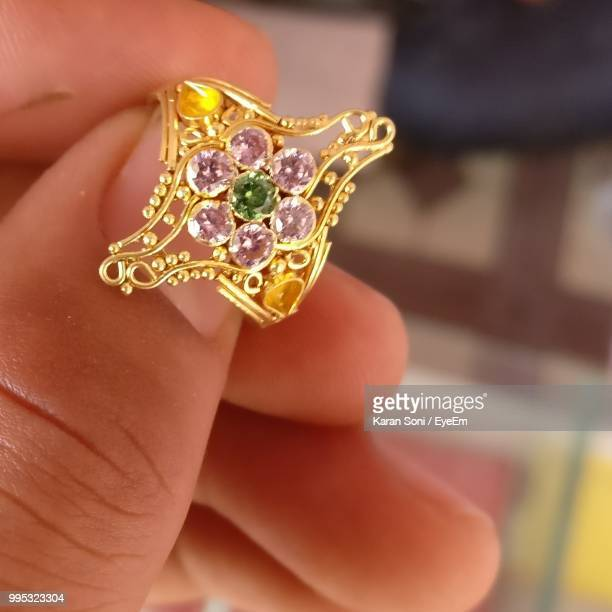 cropped hand holding diamond ring - karan soni stock photos and pictures