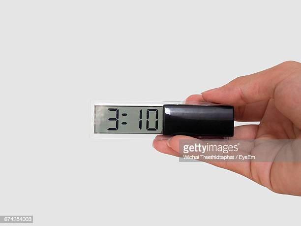 Cropped Hand Holding Digital Clock Against White Background