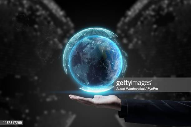 cropped hand holding digital globe over palm of hand in mid-air against abstract background - big tech stock pictures, royalty-free photos & images