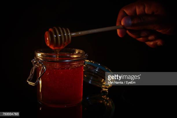 Cropped Hand Holding Dipper Over Honey In Jar Against Black Background