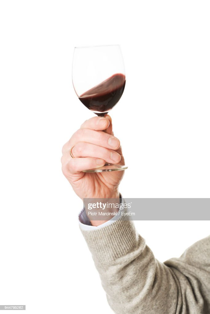 Cropped Hand Holding Drink Against White Background : Stock Photo