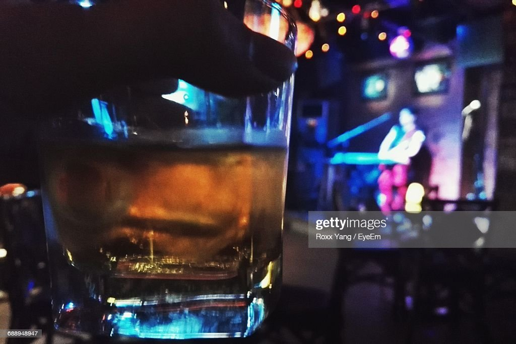 Cropped Hand Holding Drink While Musician Performing In Background At Bar : Stock Photo