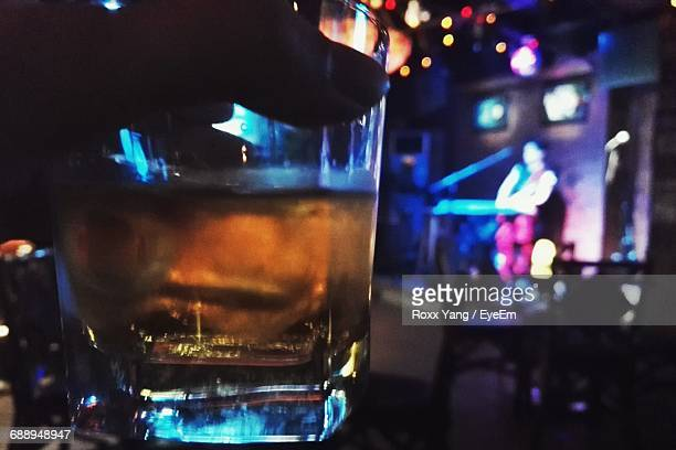 cropped hand holding drink while musician performing in background at bar - ice cube entertainer stock photos and pictures