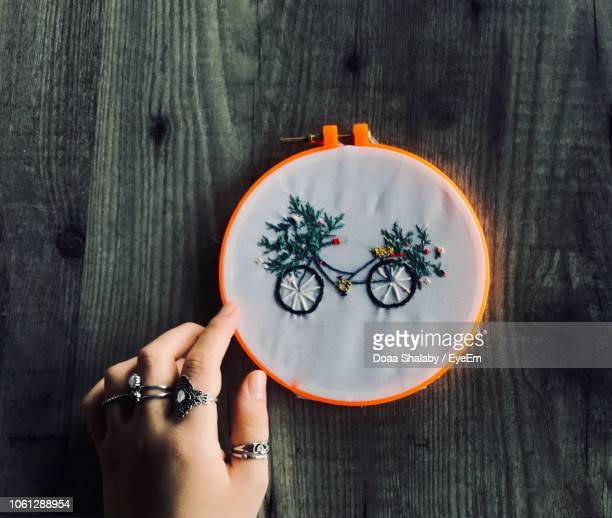 cropped hand holding embroidery ring with bicycle design on fabric - embroidery stock pictures, royalty-free photos & images